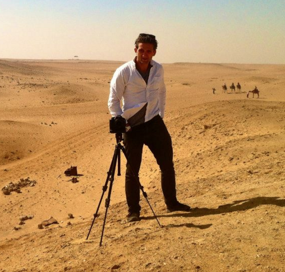 """Self-portrait of Casey Neistat standing in front of a camera on a tripod atop a sand dune in the desert with camels in the background. Apparently taken during filming """"Make It Count"""" for Nike."""